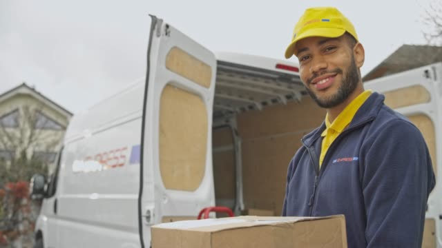portrait of a smiling male courier holding a package next to his van - manual worker stock videos & royalty-free footage