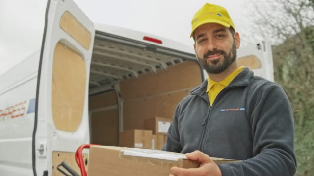 portrait of a smiling male courier with a beard holding the package next to his van - delivery person stock videos & royalty-free footage