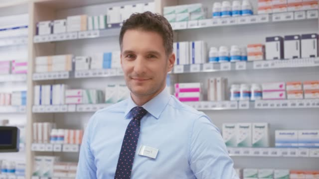 vídeos de stock e filmes b-roll de portrait of a smiling male pharmacist at the chemist's - bata cirúrgica