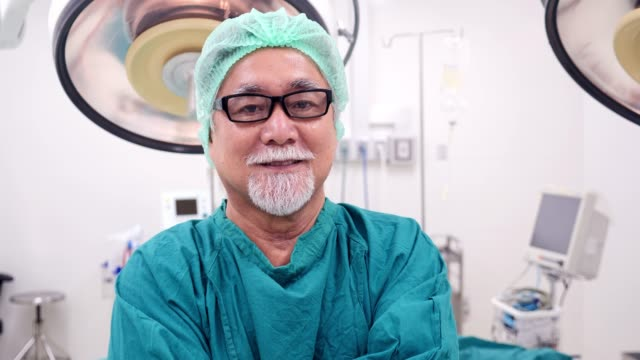 portrait of a smiling male surgeon in operating room. - anaesthetist stock videos & royalty-free footage
