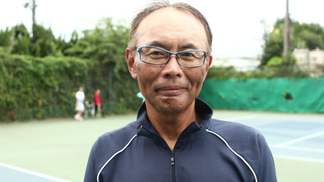 portrait of a smiling man on tennis court - 中年の男性点の映像素材/bロール