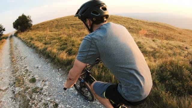 vídeos de stock e filmes b-roll de portrait of a smiling mountain biker cycling on dirt road in grass covered mountains - cavalgada de lazer