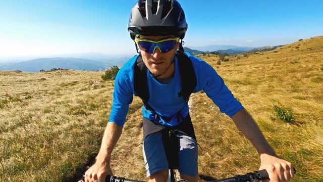 vidéos et rushes de verticale d'un vélo de montagne de sourire faisant du vélo sur le chemin de terre dans les montagnes couvertes d'herbe - caméra portable