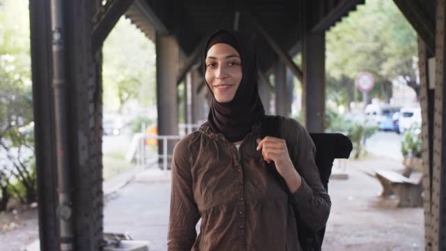 vídeos de stock, filmes e b-roll de retrato de um viajante feminino muçulmano sorridente com mochila (câmera lenta) - véu