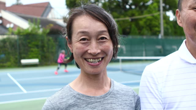 vídeos y material grabado en eventos de stock de portrait of a smiling tennis team on the court - exclusivamente japonés
