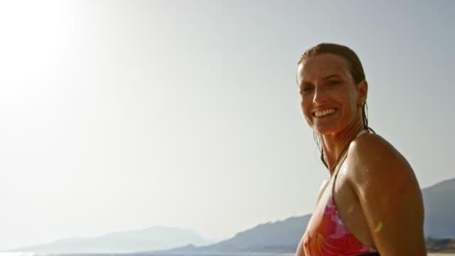stockvideo's en b-roll-footage met portret van een lachende vrouw zit op haar surfplank in de zee in de zon - bikini