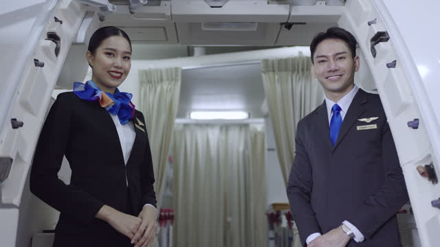portrait of a smiling young female and male flight attendant in an airplane - males stock videos & royalty-free footage