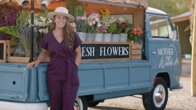 portrait of a smiling young female entrepreneur next to her flower truck at a farmers market - straight hair stock videos & royalty-free footage