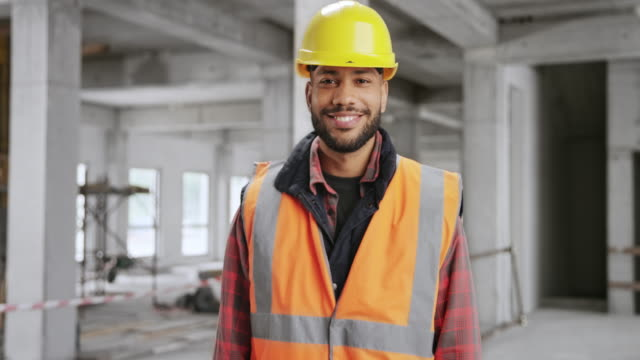 portrait of a smiling young male construction worker - work helmet stock videos & royalty-free footage