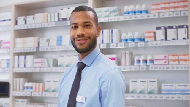 vídeos y material grabado en eventos de stock de retrato de un joven farmacéutico sonriente de pie detrás del mostrador - encuadre cintura para arriba