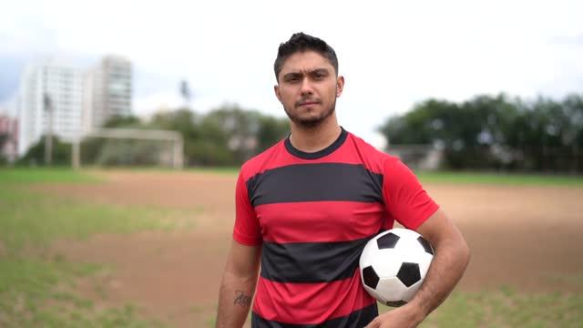 vídeos de stock, filmes e b-roll de retrato de um jogador de futebol em uniforme vermelho e preto - encarando