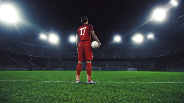 DS Portrait of a soccer player holding a ball in an empty stadium