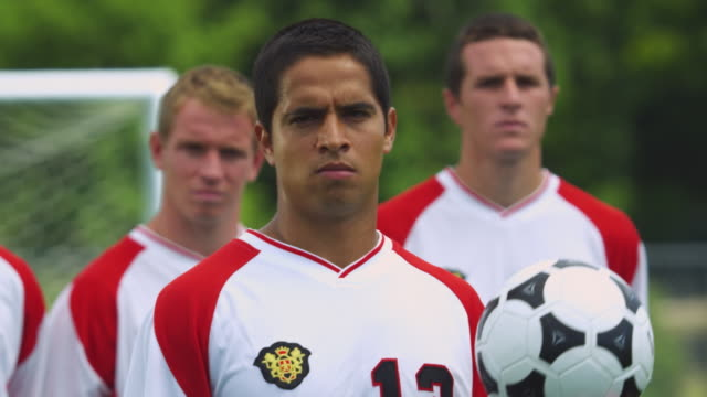 A soccer player tosses a ball in his hand while his team stands behind him.