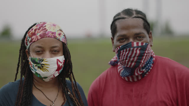slo mo cu portrait of a solemn couple looking at the camera while wearing masks - respect stock videos & royalty-free footage