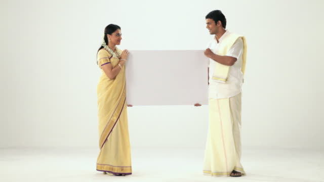 Portrait of a south Indian couple showing a placard