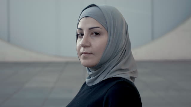 portrait of a sporty head-turning muslim woman in hijab (slow motion) - arabesque stock videos & royalty-free footage