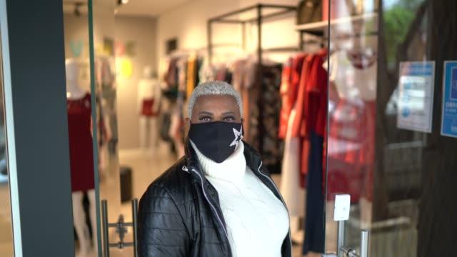 porträt eines ladenbesitzers, der eine gesichtsmaske trägt, die im eingang des ladens steht - 40 seconds or greater stock-videos und b-roll-filmmaterial