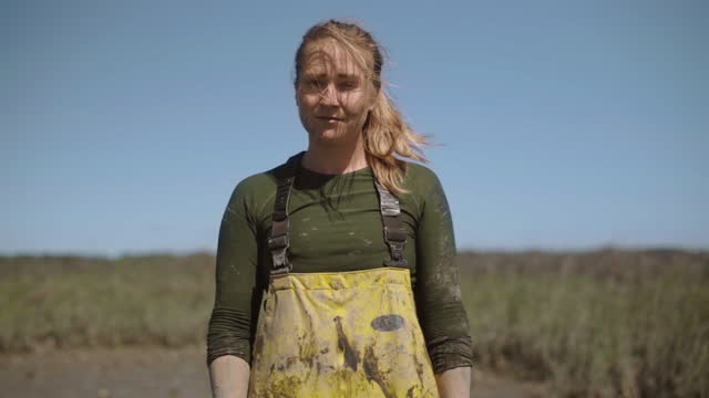 slo mo. cu. portrait of a strong fisherwoman dressed in waders looks up and stares into the camera with her hair blowing in the wind - incentive stock videos & royalty-free footage