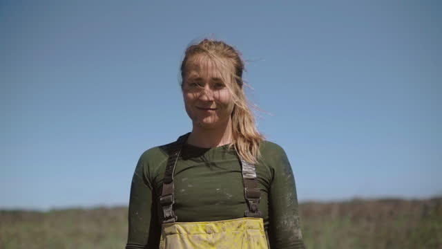 vídeos de stock e filmes b-roll de slo mo. cu. portrait of a strong fisherwoman dressed in waders smiles at the camera with her hair blowing in the wind - pescador