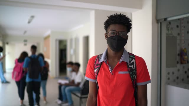 portrait of a student wearing face mask at school's patio - first day of school stock videos & royalty-free footage
