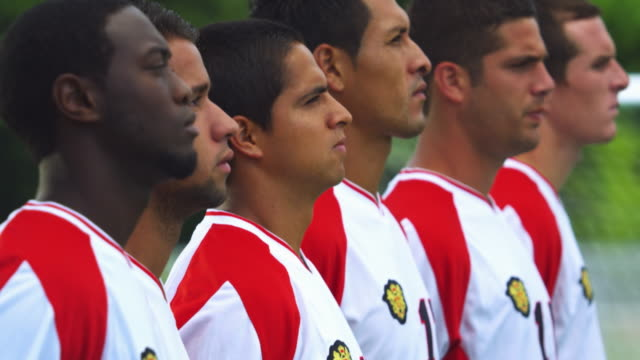 Medium profile of soccer players standing in line; camera tilts up to close-up portrait of player turning to look at camera