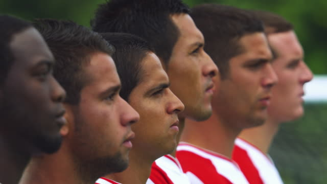 Close-up profile of soccer players standing in line; one player turns to look at camera