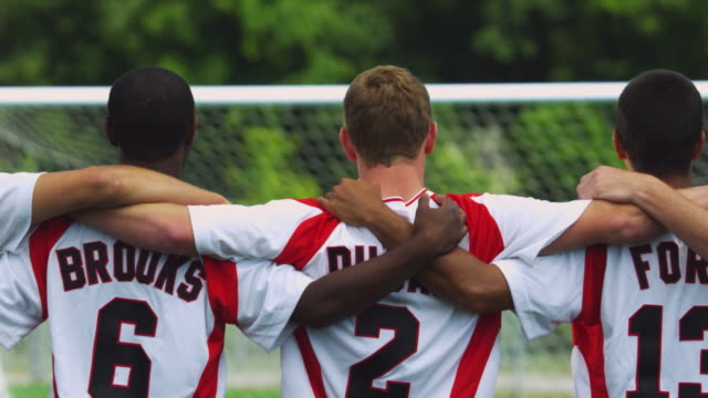 A soccer team stands in a row with their arms over each other's shoulders.