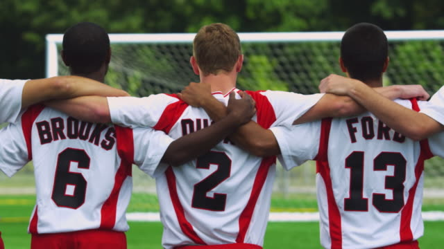 slo mo. portrait of a team of soccer players standing on a soccer field with their arms on each other's shoulders facing away from the camera - defender soccer player stock videos and b-roll footage