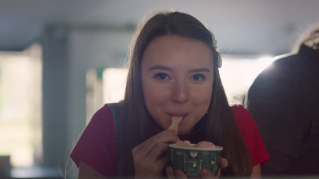 slo mo. portrait of a teenage girl eating ice cream in line at an ice cream parlor - eating stock videos & royalty-free footage