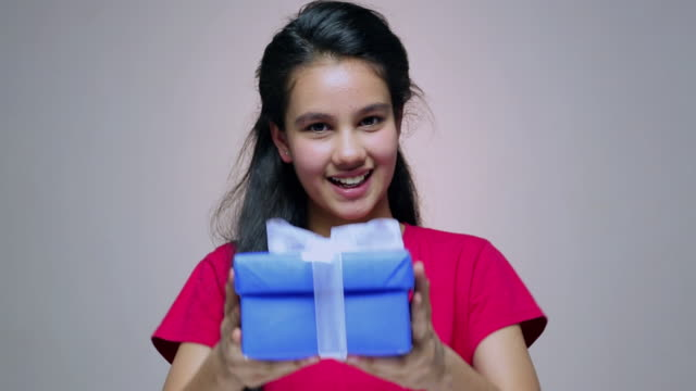 portrait of a teenage girl giving gift box  - altruismo video stock e b–roll