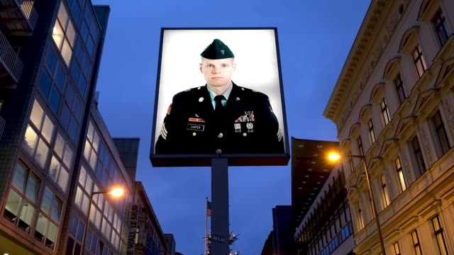 vidéos et rushes de portrait of a u.s. soldier stands illuminated at former checkpoint charlie, where u.s. and soviet tanks confronted each other in the early years of... - guerre froide