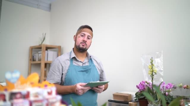 portrait of a vitiligo florist using digital tablet among flowers arrangement - apron stock videos & royalty-free footage
