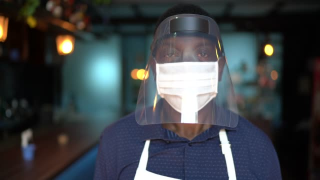 portrait of a waiter wearing protective face mask at restaurant - human face stock videos & royalty-free footage