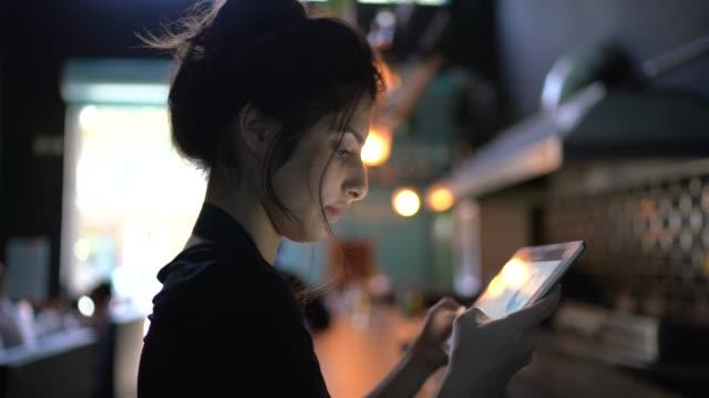 vídeos de stock e filmes b-roll de portrait of a waitress / owner using digital tablet at restaurant - empregada de mesa