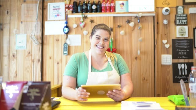 portrait of a waitress using digital tablet on checkout counter - retail occupation stock videos & royalty-free footage