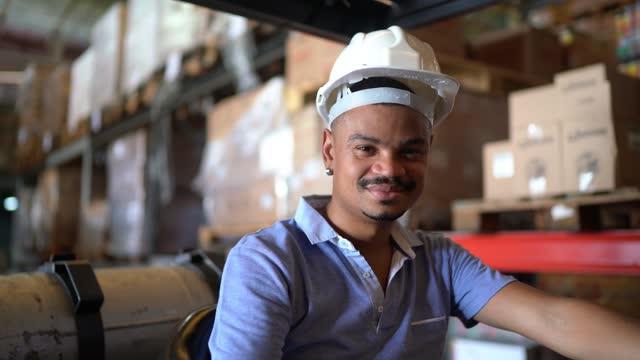 vidéos et rushes de verticale d'un ouvrier d'entrepôt conduisant un chariot élévateur - un seul homme d'âge moyen