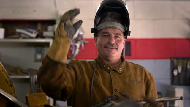 vídeos de stock, filmes e b-roll de portrait of a welder with his protective helmet - soldador