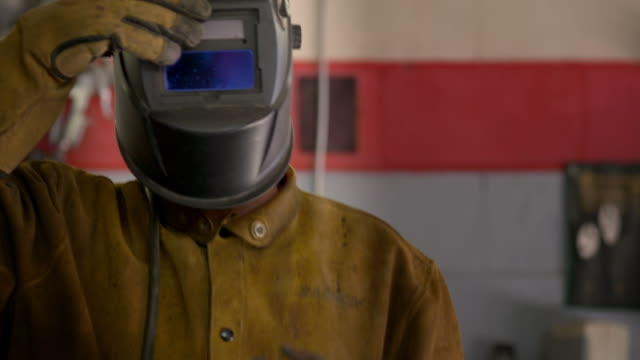 portrait of a welder with his protective helmet - effort stock videos & royalty-free footage
