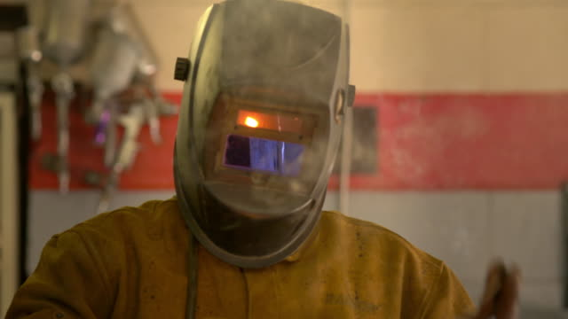 portrait of a welder with his protective helmet - grinding stock videos and b-roll footage