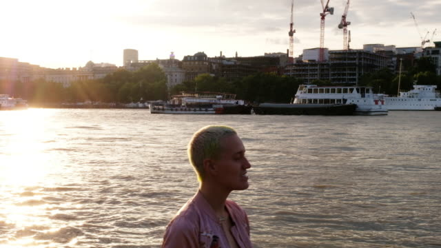 a portrait of a woman along thames river in london, england during sunset. - naga river stock videos and b-roll footage
