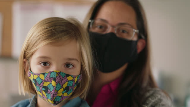 slo mo cu portrait of a woman and her young daughter sitting together and wearing protective face masks - alertness stock videos & royalty-free footage