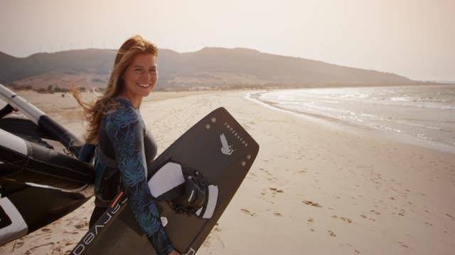 porträt einer frau hält ihren kite und kiteboard an einem sonnigen strand und lächelnd - langes haar stock-videos und b-roll-filmmaterial