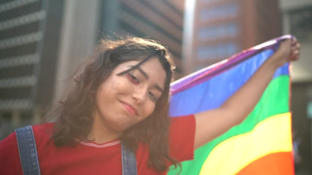 portrait of a woman holding rainbow flag during lgbtqi parade - uguaglianza video stock e b–roll
