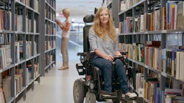 ld portrait of a woman in a wheelchair smiling in the library aisle - wheelchair stock videos and b-roll footage