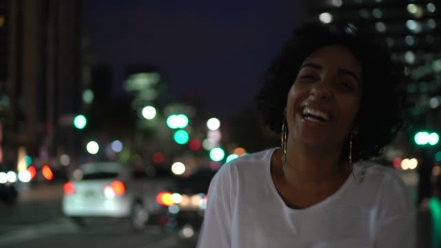 Porträt einer Frau, die nachts in der Stadtstraße lacht