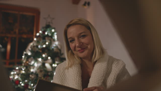 ms portrait of a woman opening a gift box on a christmas eve - low lighting stock videos & royalty-free footage