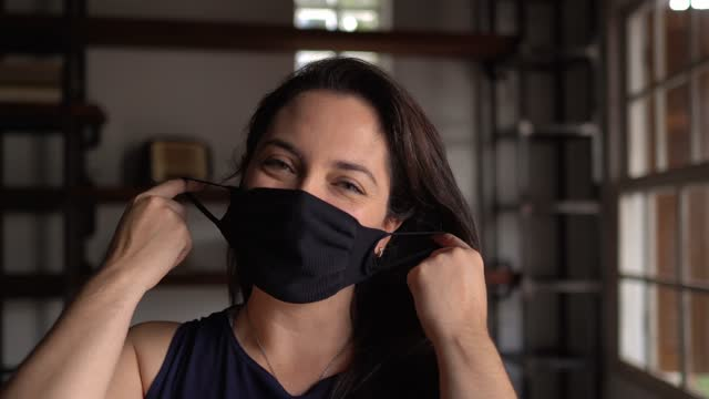 portrait of a woman removing protective face mask at home - absence stock videos & royalty-free footage