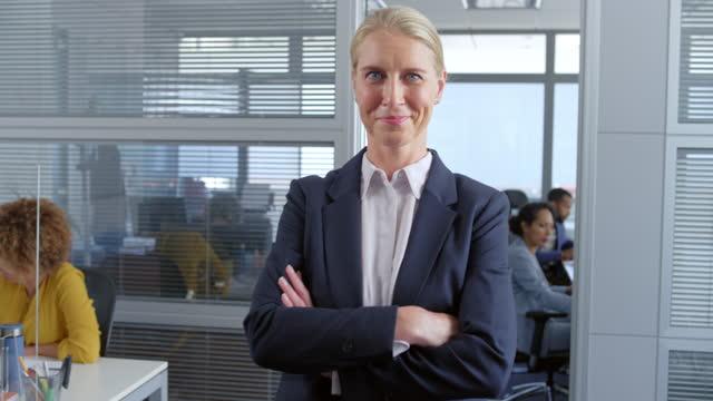 slo mo porträt einer frau, die in die kamera lächelt, während sie im büro steht - lebensziel stock-videos und b-roll-filmmaterial