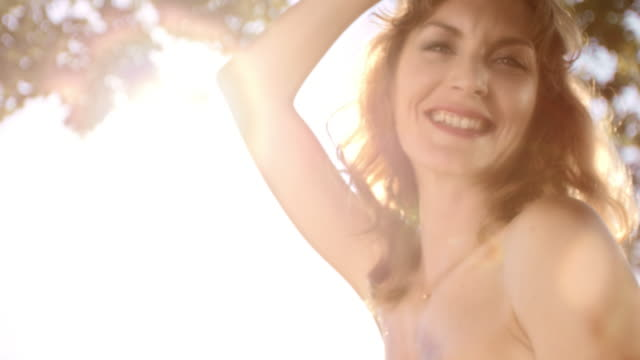 slo mo portrait of a woman smiling on a swing in sunshine - slovenia meadow stock videos & royalty-free footage