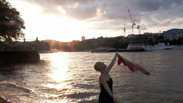 A portrait of a woman throwing her jacket in the air while walking in the Thames River in London, England during sunset.